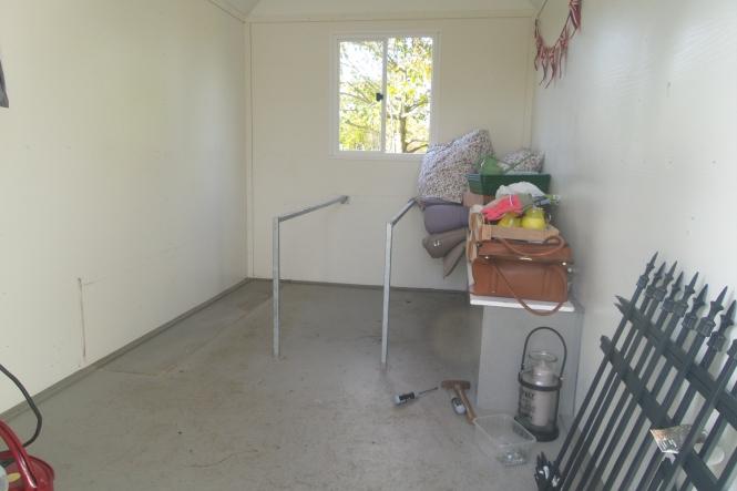 Das Innere des Bauwagens ohne eine der zwei Banke und ohne die Tischplatte. Übrig sind zwei Stahlträger des Tisches sowie die zweite Bank auf rechter Seite.